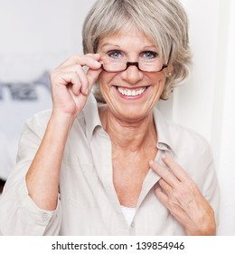 Happy attractive senior lady with a beautiful big smile wearing reading glasses and peering over the top at the viewer