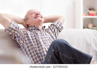 Happy attractive senior man resting and breathing sitting on a couch at home
