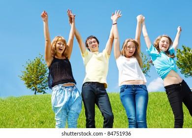 Happy attractive teenagers holding hands