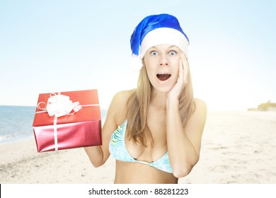 happy attractive woman in santa hat holding christmas gift at the beach
