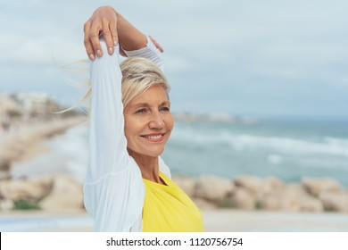 Happy attractive woman at the seaside stretching her arms over her head with a smile as she looks to the side