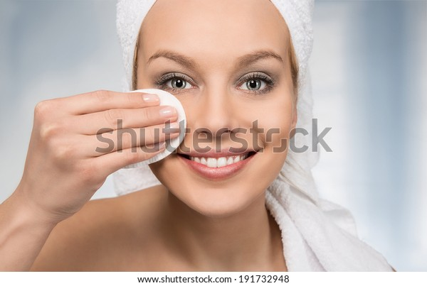 Happy attractive women removing makeup in the bathroom