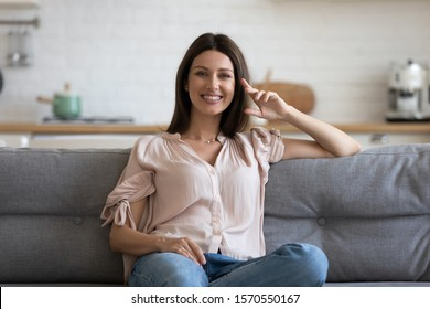 Happy attractive young adult woman housewife sitting on sofa looking at camera in modern cozy home, smiling single 30s lady beautiful face relaxing on couch alone enjoy wellbeing posing for portrait