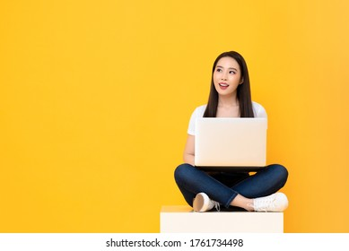 Happy attractive young Asian woman with laptop computer sitting cross legged and looking at empty space on yellow studio background