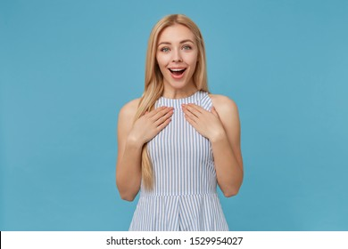 Happy attractive young blonde woman lady with casual hairstyle keeping palms on her chest while standing over blue background, looking at camera joyfully with wide smile