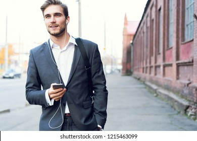 Happy attractive young businessman walking and using mobile phone outdoors