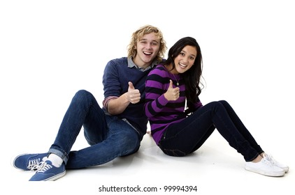 happy and attractive young couple giving the thumbs up sign