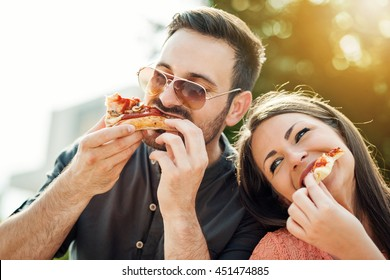 Happy attractive young couple romantically eating a fresh pizza outdoors.