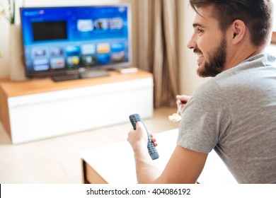 Happy attractive young man watching tv and using remote control at home