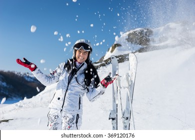 Happy attractive young skier in a white ski suit and helmet tossing snow in the air with her gloved hands and her skis standing upright alongside