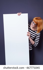 Happy attractive young woman in glasses standing holding and reading a blank white sign with copy space in vertical format over a blue background