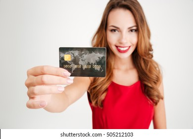 Happy attractive young woman holding and showing credit card over white background
