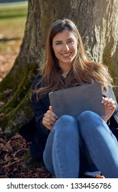 Happy attractive young woman seated under a tree leaning on the trunk with a tablet resting on her knees doing e-learning and giving the camera a friendly warm smile