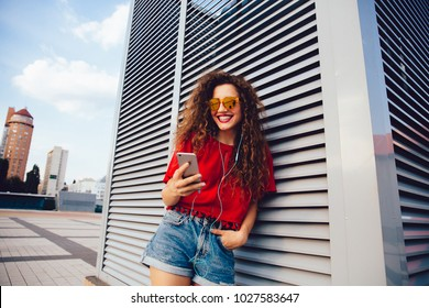 Fröhliche junge Frau in einer Sonnenbrille, die Musik in Ohrhörern hört, Smartphone-Bildschirm beim Spaziergang in der Stadt ansieht. In stilvollen Kleider verkleidet.