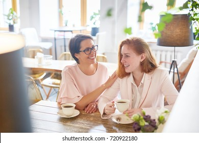 Happy aunt and niece relaxing in cafe and enjoying talk by cup of coffee