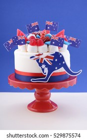Happy Australia Day celebration cake with flags, marshmallow and candy decorations on a red cake stand on a white table against a blue background.