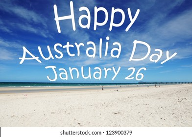 """Happy Australia Day January 26"" message written across blue sky over white sandy Australian beach."
