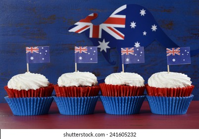 Happy Australia Day January 26 party food with red velvet cupcakes with kangaroo flag on dark red and blue vintage rustic recycled wood background.
