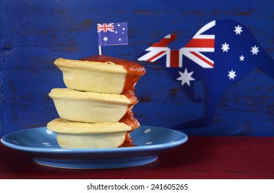 Happy Australia Day January 26 party food with iconic meat pies and tomato sauce on dark red and blue vintage rustic recycled wood background.