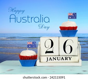 Happy Australia Day, January 26, theme white wood vintage calendar and red, white and blue cupcakes with view of Australian beach background, with sample text greeting message.