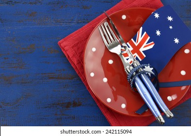 Happy Australia Day, January 26, theme table setting with red polka dot plate and Australian flag decoration on dark blue wood background.