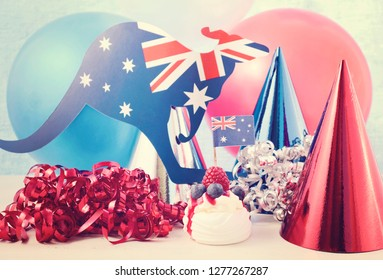 Happy Australia Day Party in red, white and blue theme with mini pavlova and party decorations, with applied vintage wash filter.