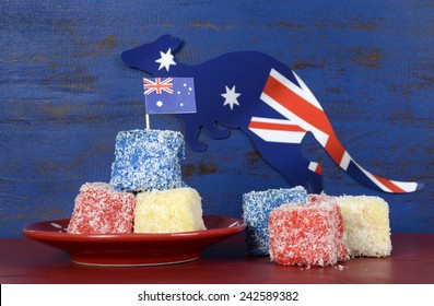 Happy Australia Day red, white and blue lamingtons on red and blue dark recycled wood background.
