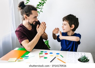 Happy autism boy during therapy with school counselor, learning and having fun together