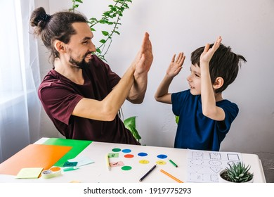 Happy autism boy during therapy with school tutor, learning and having fun together