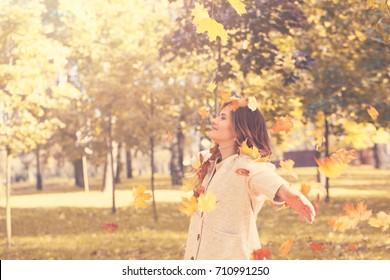 Happy Autumn. Beautiful Woman  Fashion Model Having Fun in Fall Park Outdoors