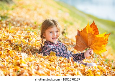 Happy autumn kid having fun with leaves outdoor in park. Falling leaves natural background - Shutterstock ID 1801398187
