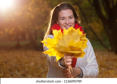 Happy autumn time. Positive beautiful woman wearing coat and red scarf with yellow fall leaves on the background of nature park