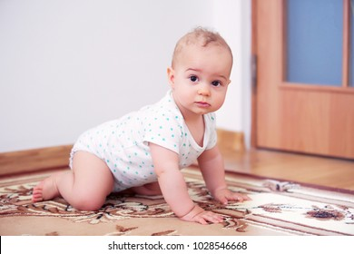 Happy baby boy (1 year old) playing on floor in children's room.