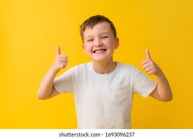 Happy baby boy of 7 years in a white T-shirt on a yellow background
