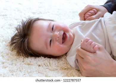 Happy baby boy with being cared for by his parents