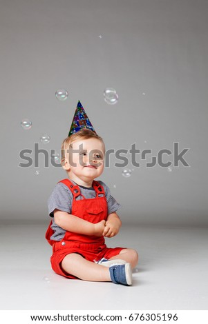 Happy Baby Boy With Birthday Hat And Foam Balloons Studio Shot