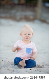 happy baby boy with blond hair and blue eyes in jeans and t-shirt sitting on the beach