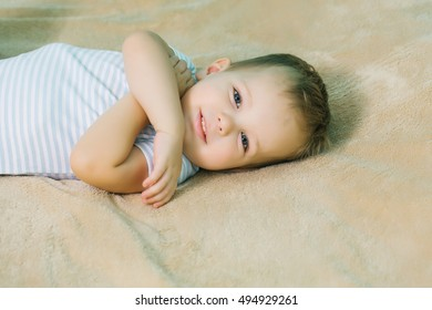 Happy baby boy with blue eyes and blond hair in romper smiles on beige bed cover