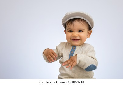 Happy baby boy with a cap, laughing and looking at camera