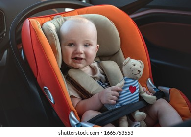 Happy baby boy in the car seat.