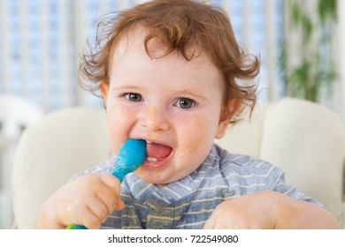Happy baby boy eating by himself on high chair