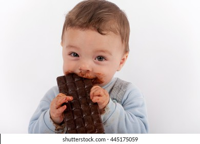 Happy baby boy eating chocolate