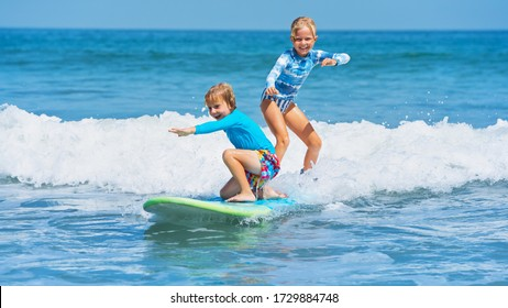 Happy baby boy and girl - young surfers ride with fun on one surfboard. Active family lifestyle, kids outdoor water sport lessons, swimming activity in surf camp. Sea beach summer holiday with child.