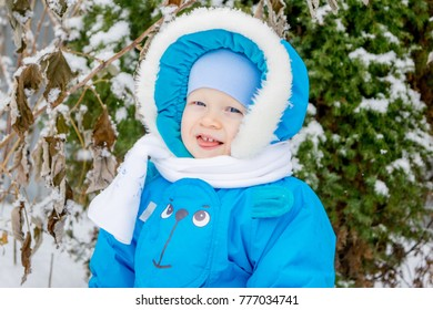 Happy baby boy is glad to snow - winter holiday outing for children