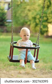 Happy baby boy having fun on a swing ride at a playground a summer day