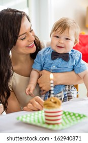 Happy baby boy and mother with birthday cake on table at home