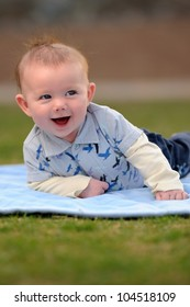 Happy Baby Boy Outside on Blanket. Smiling three-month old baby boy laying on a blue blanket outside. Shallow DOF.
