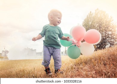 Happy baby boy playing with ballons on green grass