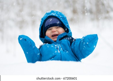 Happy baby boy playing in the snow