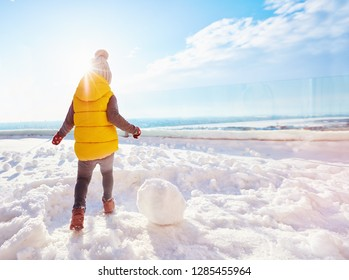 happy baby boy playing snowballs at sunny winter day
